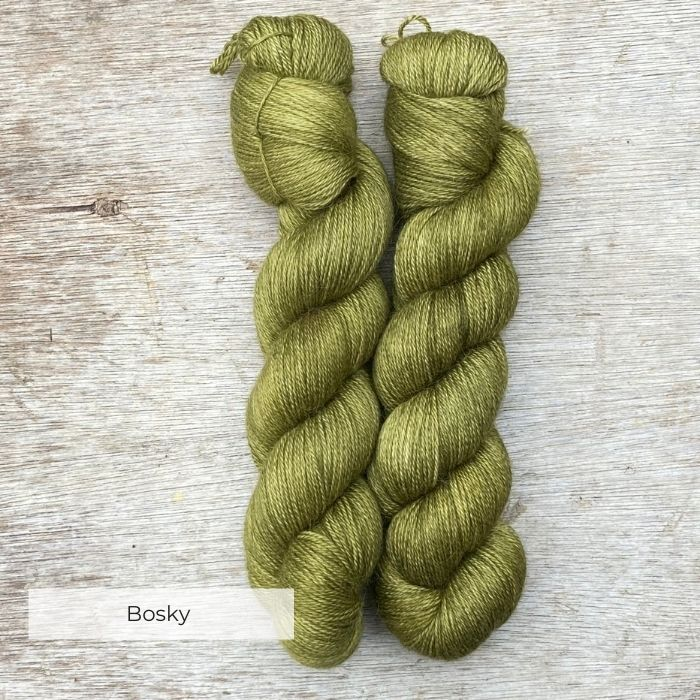 Two skeins of moss green yarn on a wood background