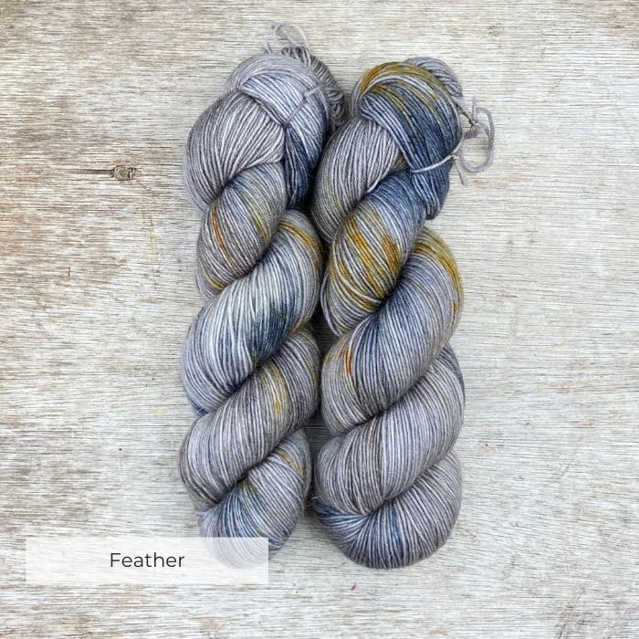 Two hanks of yarn blue and gold splashes on a light brown base