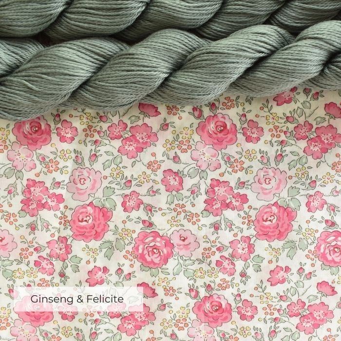 Two skeins of soft sage green yarn laying on a piece of pink floral Tana Lawn