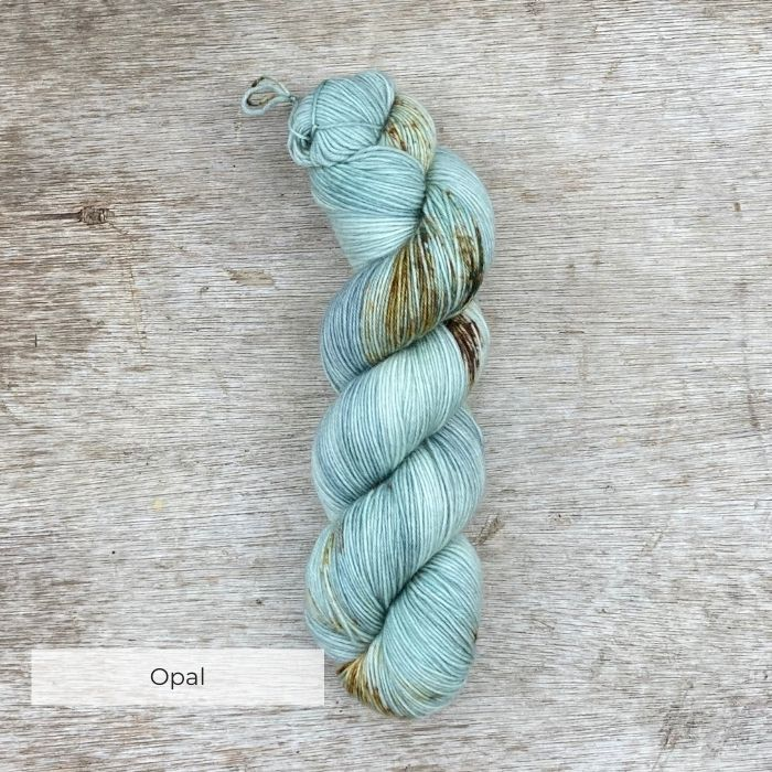 A hank of sock yarn dyed in shades of mint, pearl grey and blue with speckles of dark green, rust and brown