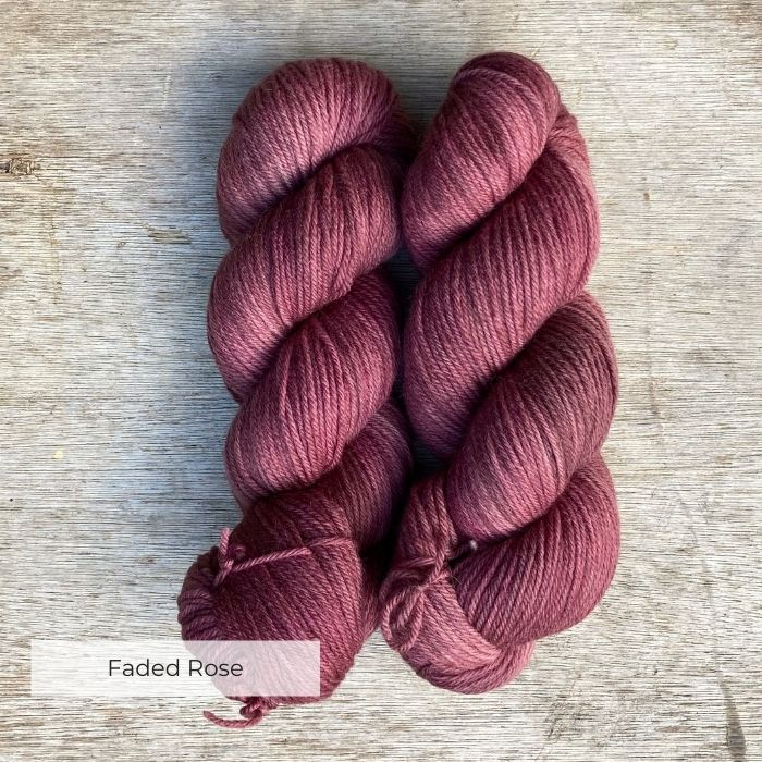Two skeins of a soft rose yarn on a wooden background