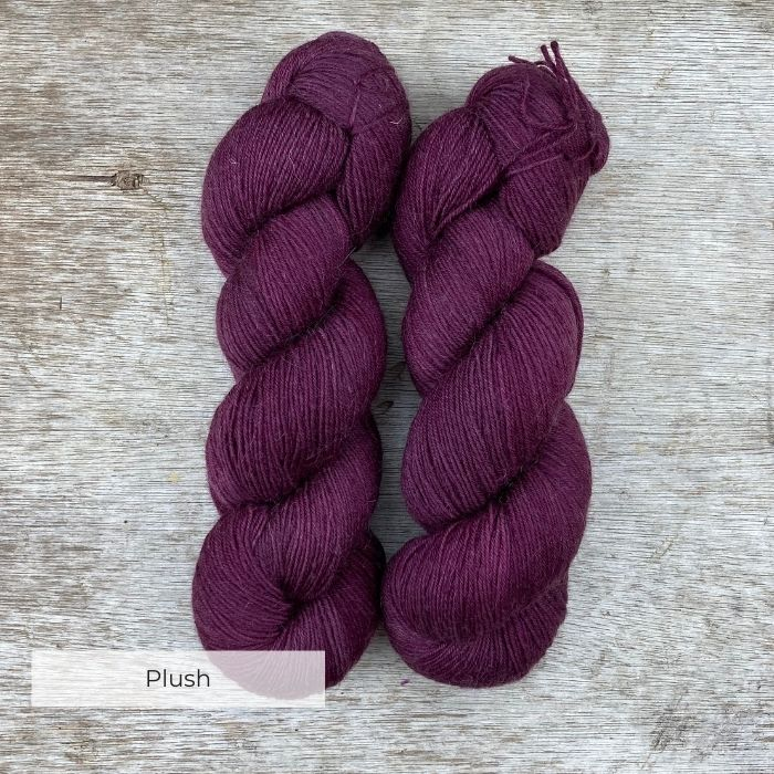Two skeins of yarn the colour of faded burgundy and plum