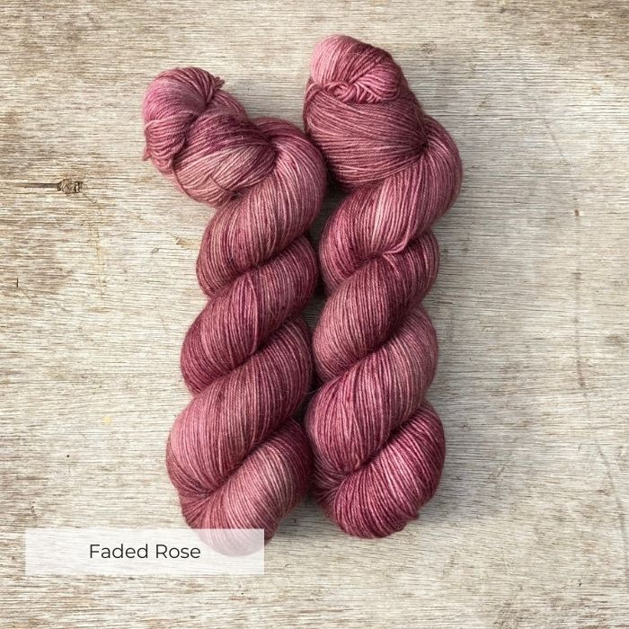 Two skeins of yarn dyed a deep rose pink