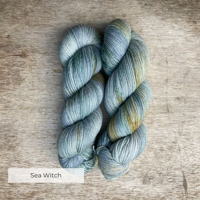 Two skeins of skeins of yarn dyed in shades of pale blue, green and grey with speckles of gold and deep green
