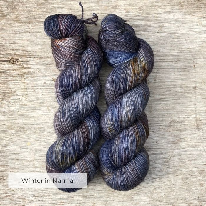 Two hanks of yarn in shades of blue, brown, gold and plum
