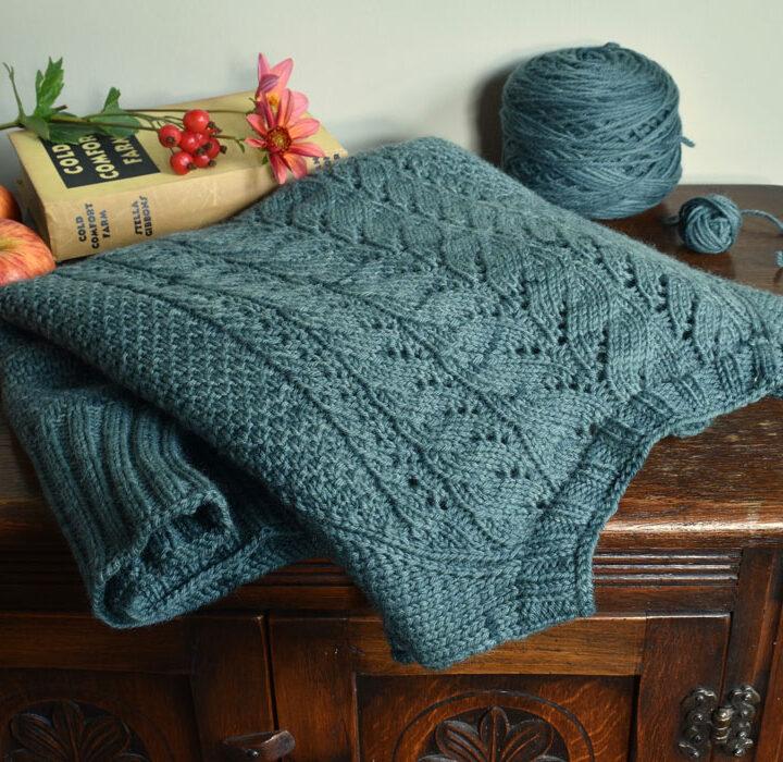 A folded sweater on a dark side cupboard